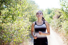 Girl runs in the forest and listens to music Stock Image