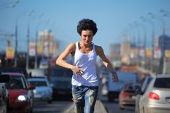 Girl runs on highway middle in city Stock Photos