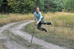 Girl runs and jumps with a cane Stock Photography