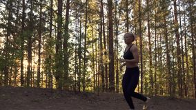 Girl runs lightly uphill. Beautiful sportswoman in training in the woods at sunset. Young girl on run training in forest. Athlete in sportswear on training stock footage