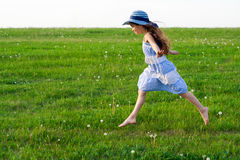 Girl runs on meadow with dandelions Stock Photos