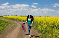 Girl runs near yellow rape meadow Royalty Free Stock Images