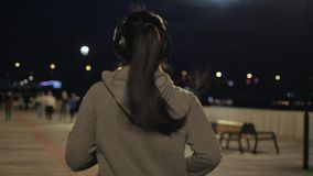 Girl runs through the night city and listens to music on headphones. outdoor sports. night run stock footage