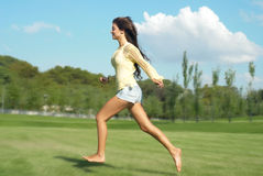 Girl runs through the park Stock Images