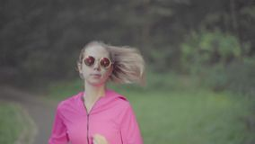 Girl runs through park. Girl runs through the park in morning stock footage