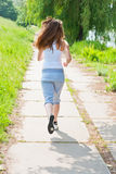 Girl runs in park view from the back. Royalty Free Stock Images