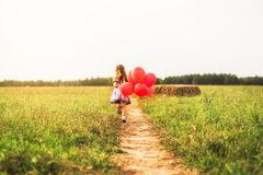 Girl runs with red balloons in the summer in nature. One girl runs with red balloons in the summer in nature royalty free stock photo