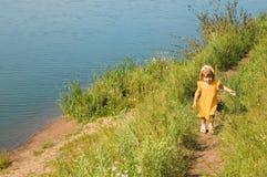 The girl runs on river bank. The girl runs on road along river bank stock photo