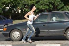 Girl runs on road among cars Stock Photo