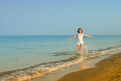 The girl runs on a sandy beach Stock Image