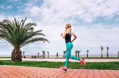 Girl runs on the sea embankment. Active life style Royalty Free Stock Photos