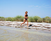 The girl runs on seacoast. The suntanned girl runs on coast of sea of Azov Royalty Free Stock Photo