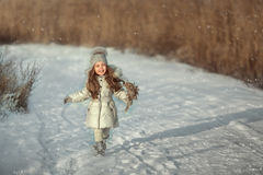 Girl runs on a snowy road Stock Photos