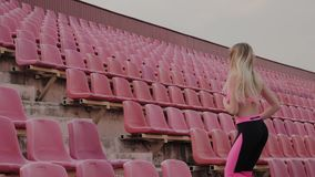 The girl runs in the stadium among the seats, training in the fresh air. stock video
