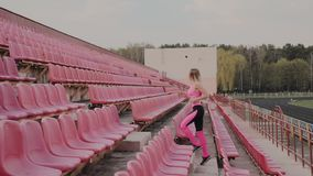 The girl runs in the stadium among the seats, training in the fresh air. The girl runs in the stadium among the seats, training in the fresh air stock footage