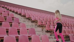 The girl runs in the stadium among the seats, training in the fresh air. stock video footage