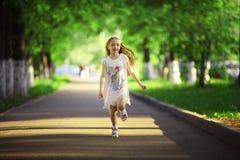 Girl runs at sunny park Stock Images