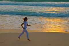 Girl runs at sunset along strip of surf Royalty Free Stock Photography