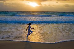 Girl runs at sunset along strip of surf Royalty Free Stock Images