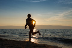 Girl runs at the sunset near Baikal lake. A silhouette of a running girl in sunset stock image