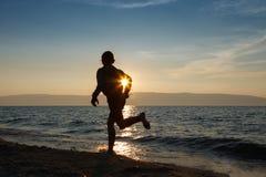 Girl runs at the sunset near Baikal lake. A silhouette of a running girl in sunset Stock Image
