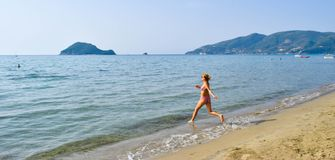 Girl running into the sea. royalty free stock photo