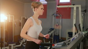 Girl runs on treadmill. Active girl in gym runs on treadmill. Athlete cardio activity on treadmill stock video