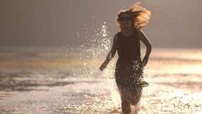 Girl runs on water slow motion stock footage