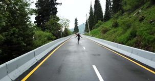 The girl runs on the wet asphalt. Mountainous terrain, the sides of the road are spruce and green grass. Shooting from a drone, draw follows the girl. Yellow stock footage