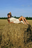 Girl in a rural clothing lying on the haystack Royalty Free Stock Image