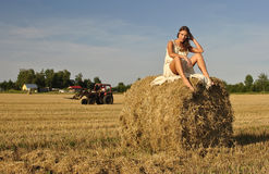 Girl in a rural clothing sitting on the haystack Royalty Free Stock Image