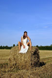 Girl in a rural clothing sitting on the haystack Royalty Free Stock Images
