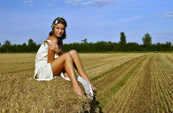 Girl in a rural clothing sitting on the haystack Stock Photography