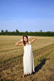 Girl in a rural clothing standing on the field Royalty Free Stock Images