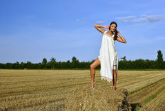 Girl in a rural clothing standing on the haystack Stock Photo