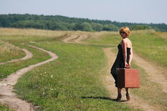 Girl on the rural road with retro case Stock Photo