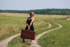 Girl on the rural road with retro case Stock Photography