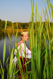 Girl in rushy lake. Girl stand in rashy lake and look to You at sunset Royalty Free Stock Image
