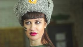 Girl in Russian army uniform. Portrait of a young beautiful girl in the uniform of the red army on dark gray background stock footage