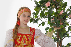 Girl in  russian costume next to a flowering tree Royalty Free Stock Photos