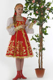 Girl in  russian costume next to a flowering tree Stock Photo