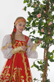 Girl in  russian costume next to a flowering tree Stock Photos