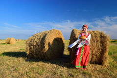 Girl in russian dress on the hay with bread Stock Image