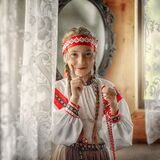 A girl in a Russian dress is holding a Rowan berry beads