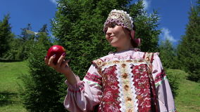 Girl in Russian folk costume contemplate red apple stock footage