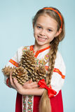 Girl in Russian folk costume holding pine cones. Beautiful girl in a traditional Russian folk costume holding pine cones. Girl seven years royalty free stock image
