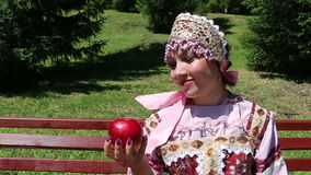 Girl in Russian folk costume and Red Apple stock video footage