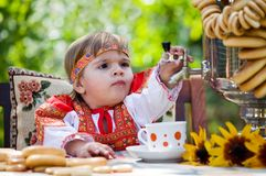 Girl in Russian national dress drinks tea Royalty Free Stock Photos