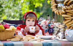 Girl in Russian national dress drinks tea Stock Photo