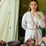 Girl in Russian national dress, standing behind the counter of a pottery shop royalty free stock photo